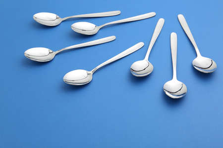 Composition with clean tablespoons on color background Archivio Fotografico
