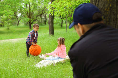 Uomo adulto sospettoso che spia i bambini al parco. Bambino in pericolo