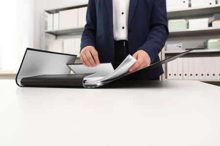 Woman working with documents at table in office, closeup
