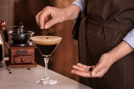 Woman preparing Espresso Martini on bar counter, closeup. Alcohol cocktail