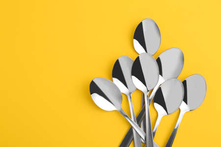 Flat lay composition with clean tablespoons and space for text on color background Archivio Fotografico