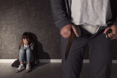 Man with unzipped pants and scared little girl indoors. Child in danger
