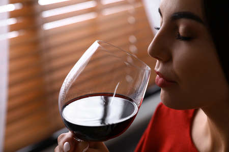 Woman with glass of luxury red wine indoors, closeup view. Space for text