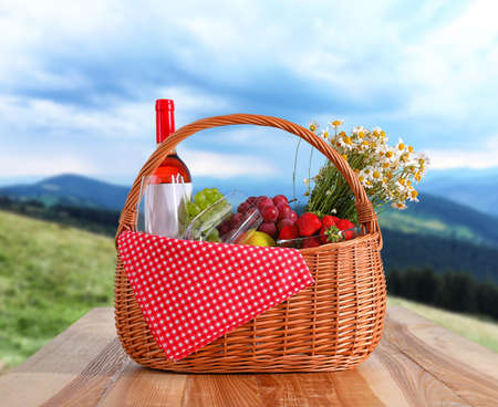 Picnic basket with wine and products on wooden table outdoors