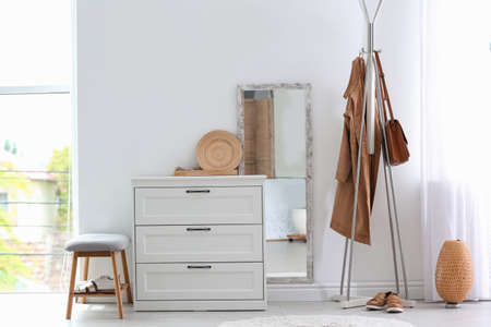 Modern hallway interior with chest of drawers and clothes on hanger stand. Space for text Stock Photo