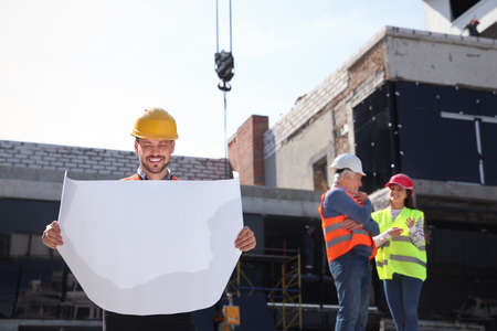 Foreman with drafting and professional engineers in safety equipment at construction site. Space for text