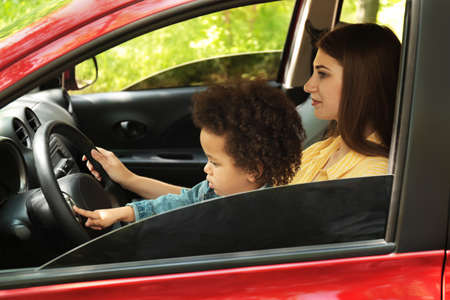 Mother with cute little daughter driving car together. Child in danger