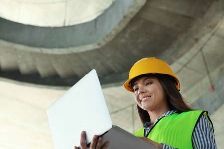 Professional engineer in safety equipment with laptop at construction site. Space for text