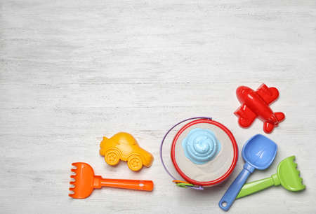 Flat lay composition with beach toys on white wooden background. Space for text