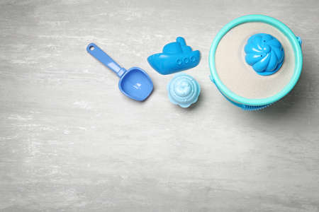 Flat lay composition with beach toys on light background. Space for text