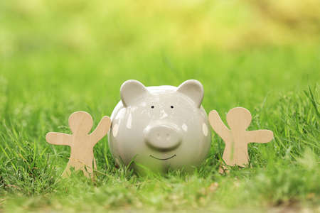 Cute piggy bank and wooden people on green grass in park 스톡 콘텐츠