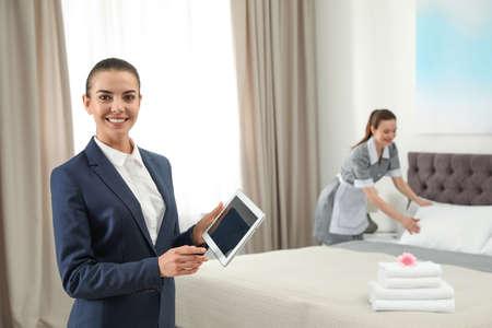 Gerente de limpieza con tableta comprobando el trabajo de limpieza en la habitación del hotel. Espacio para texto