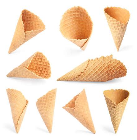 Insieme dei coni gelato croccanti vuoti del wafer su fondo bianco. Cibo dolce