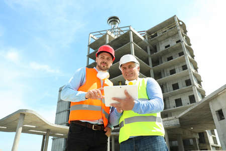 Professional engineer with tablet and foreman in safety equipment at construction site