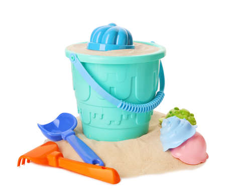 Plastic beach toys on pile of sand, white background