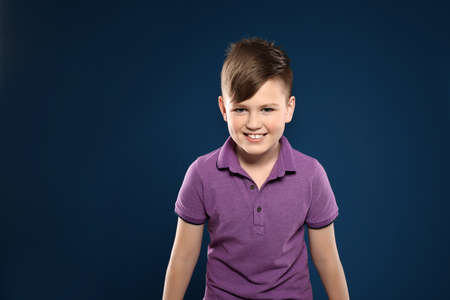 Portrait of emotional little boy on color background