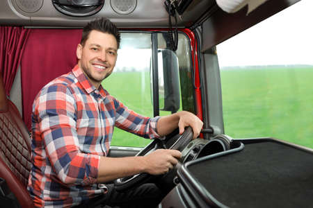 Professional driver sitting in cab of modern truck