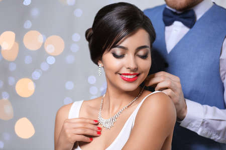 Man putting elegant jewelry on beautiful woman against blurred background. Space for text