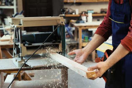 Working man using thickness planer at carpentry shop, closeup