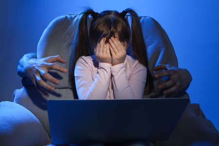 Stranger reaching frightened little child with laptop on color background. Cyber danger Stock Photo