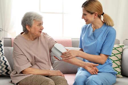 Nurse measuring blood pressure of elderly woman indoors. Assisting senior people
