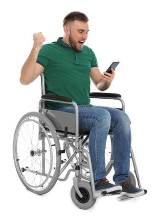 Feliz joven en silla de ruedas con teléfono móvil aislado en blanco Foto de archivo