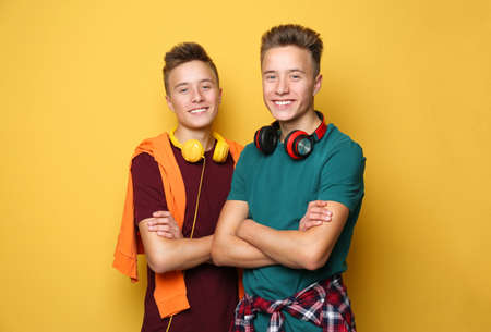 Teenage twin brothers with headphones on color background Banque d'images