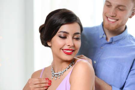 Man putting elegant jewelry on beautiful woman against light background 免版税图像