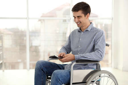 Young man in wheelchair using mobile phone near window indoors