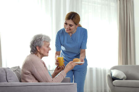 Nurse serving breakfast to elderly woman indoors, space for text. Assisting senior people Фото со стока
