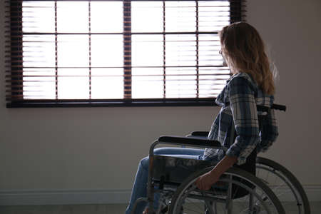 Young woman in wheelchair near window indoors