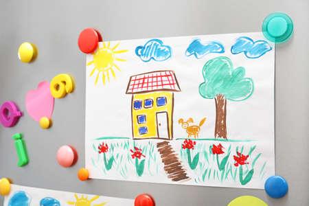 Kinderzeichnung und Magnete an der Kühlschranktür als Hintergrund Standard-Bild