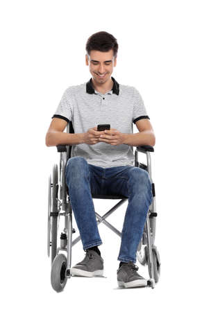 Young man in wheelchair using mobile phone isolated on white Imagens