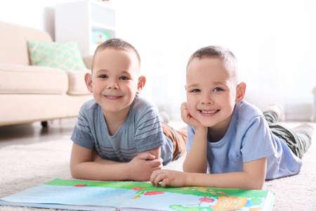 Portrait de mignons frères jumeaux avec livre sur marbre dans le salon