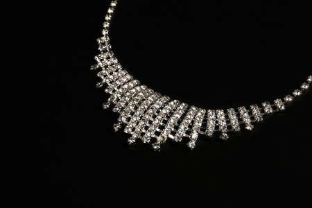 Stylish necklace with gemstones on black background, closeup. Luxury jewelry