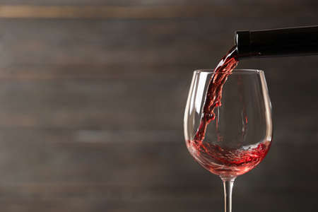 Pouring red wine into glass from bottle against blurred wooden background, closeup. Space for text