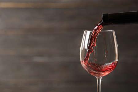 Vino rosso di versamento in vetro dalla bottiglia contro fondo di legno vago, primo piano. Spazio per il testo