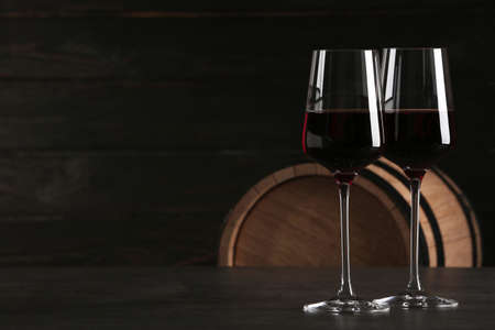 Glasses of red wine and wooden barrel on background. Space for text
