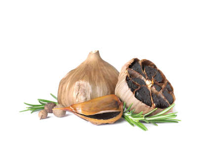 Aged black garlic with rosemary on white background