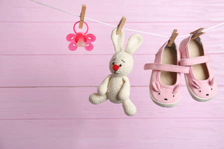 Pair of shoes, pacifier and toy bunny on laundry line against wooden background. Baby accessories