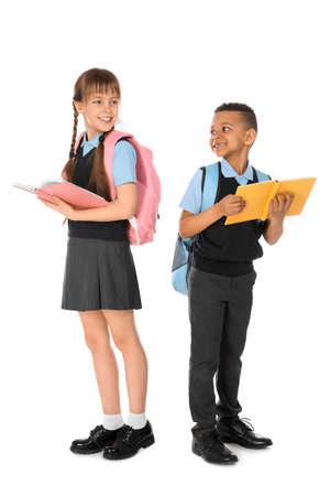Retrato de cuerpo entero de niños lindos en uniforme escolar sobre fondo blanco. Foto de archivo