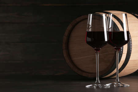 Glasses of red wine and wooden barrel on table against dark background. Space for text
