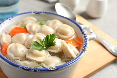 Bowl of tasty dumplings in broth on table, closeup. Space for text