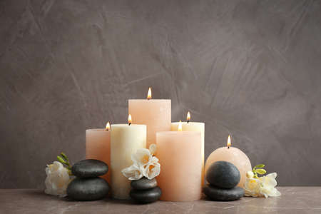 Beautiful composition with candles, stones and flowers on table against grey background