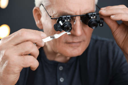 Male jeweler evaluating precious gemstone in workshop, closeup 版權商用圖片