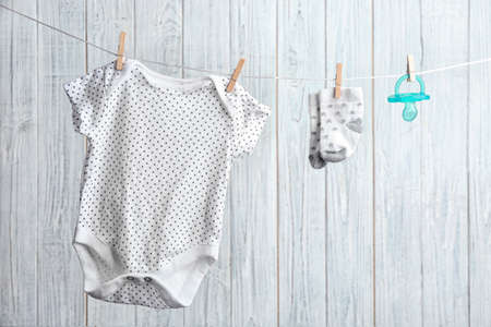 Bodysuit, pair of socks and pacifier on laundry line against wooden background. Baby accessories Standard-Bild