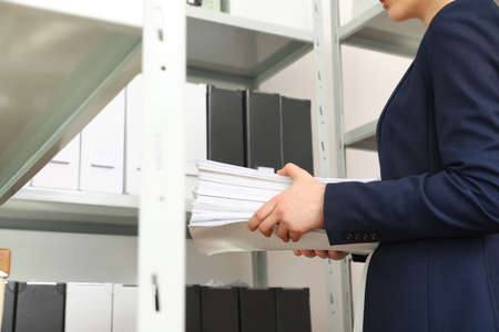Female worker with documents in office, closeup