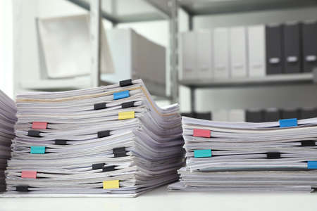 Stacks of documents with paper clips on office desk