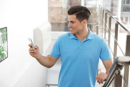 Portrait of handsome man with mobile phone on stairs in room