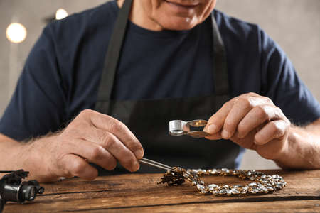 Male jeweler evaluating necklace at table in workshop, closeup 版權商用圖片